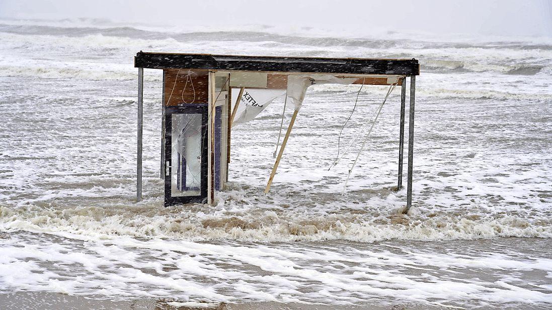 Stormschade op het strand bij Castricum, onderdelen van strandhuisjes vliegen rond, strandpaviljoen dreigt in zee te verdwijnen [video]