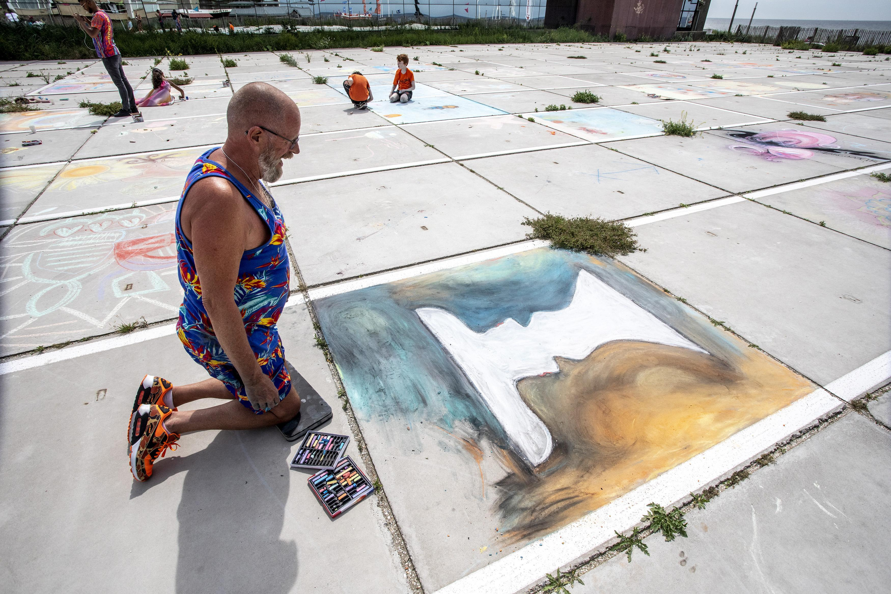 Krijtfestival Zandvoort: Kunstenaars en publiek leven zich uit op betonplaten Badhuisplein