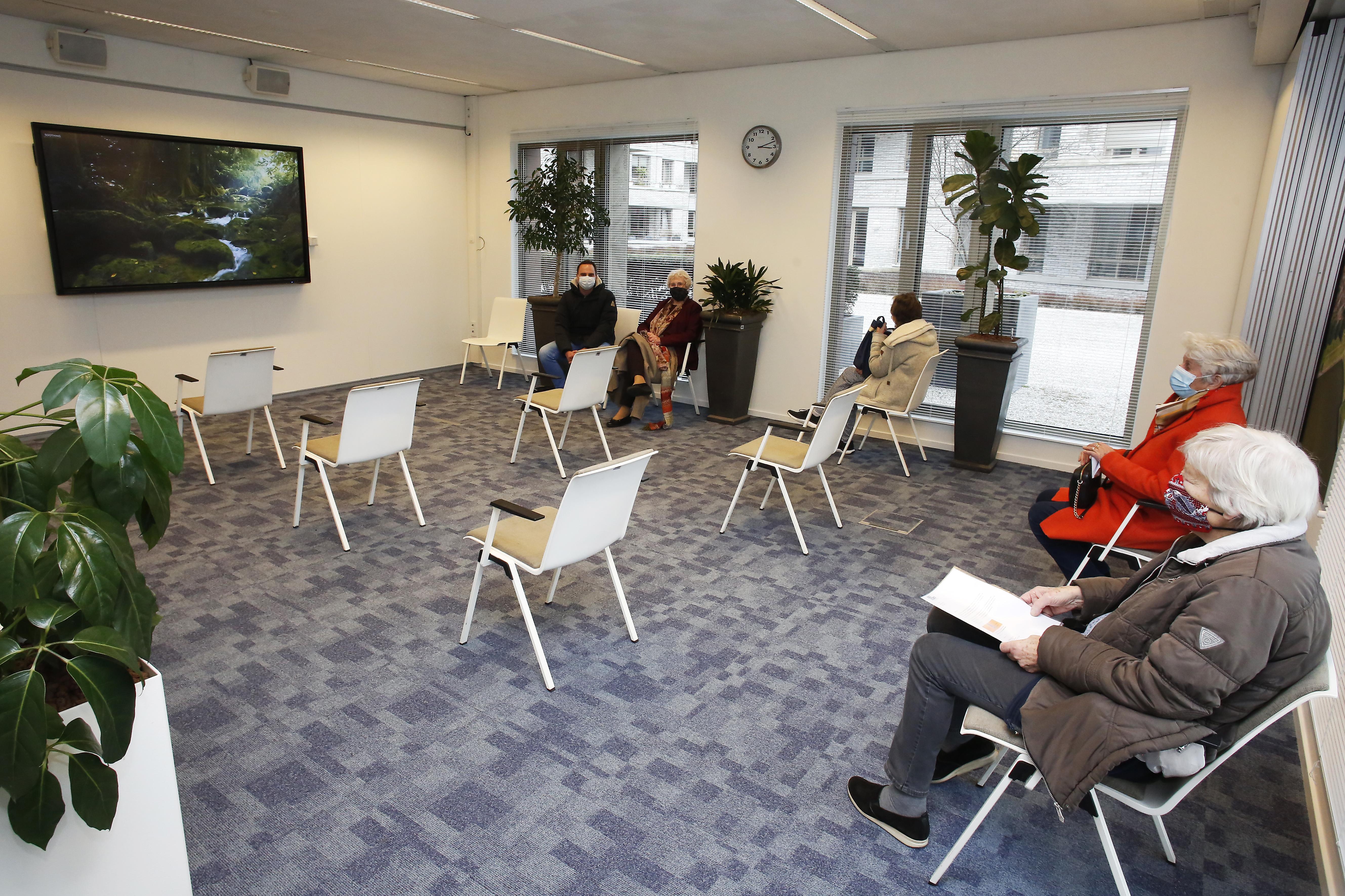 Bij GGD in Bussum geen koukleumende ouderen buiten; Aan de arm mee naar binnen en wachtruimte met rustgevende natuurbeelden